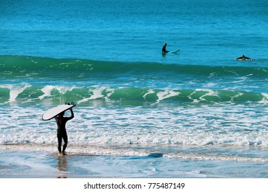 A man carrying his board to surf with other surfers on the beach of El Palmar, on the coasts of Cadiz, Spain