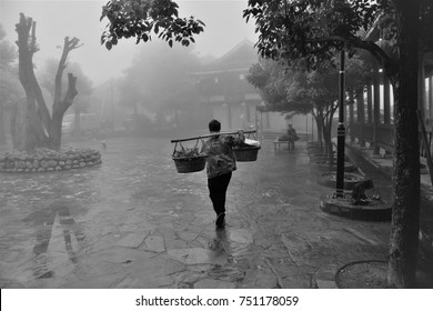 Man carrying his bundles on his shoulders assist with a pole in the China market