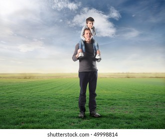 Man carrying his son on his shoulders on a green meadow