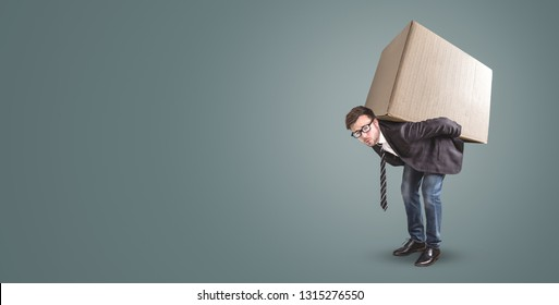 A man is carrying a large cardboard box - isolated on a neutral background with copy space