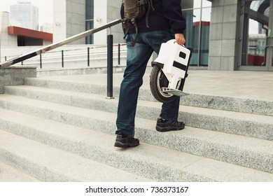 Man carrying one wheel  scooter on the stairs obstacle for personal eco transport. Mono cycle in the city. Close-up of a man.
