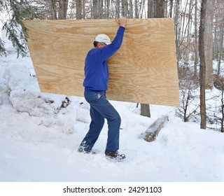 Man carrying a sheet of plywood through the snow