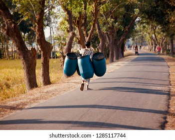A man carrying some plastic drums walking on the road
