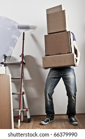 Man Carrying Stacked Boxes on moving day, desaturated image