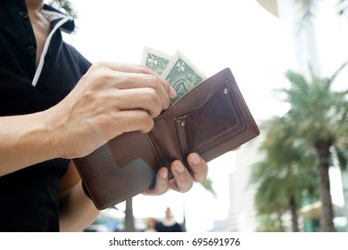 Man carrying a wallet in hand, the dollar