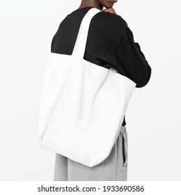 Man carrying white reusable shopping bag studio shoot