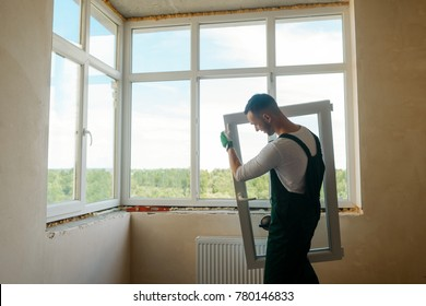 Man is carrying a window sash using a vacuum lifter. Window installation in an apartment.
