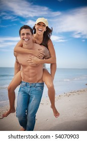 Man carrying woman on a beach, both smiling