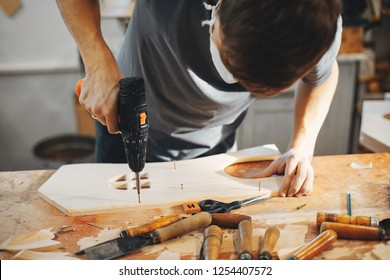 A man carves a tree. The carpenter works with drill in a studio. An engineer provides a tree shape