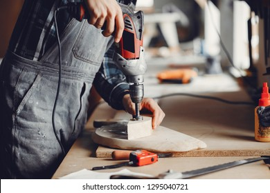 A man carves a tree. The carpenter works with a drill in a studio. An engineer provides a tree shape