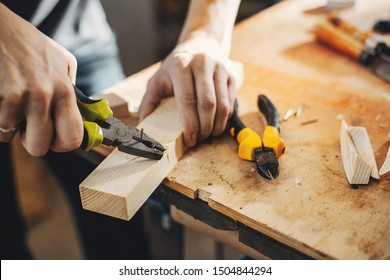 A man carves a tree. The carpenter works with pliers in a studio. An engineer provides a tree shape