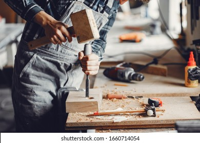 A man carves a tree. The carpenter works with a hammer in a studio. An engineer provides a tree shape