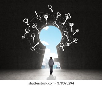 A man with a case standing in front of a huge keyhole, many keys drawn around it, city and sky seen through it. Black background. Back view.  Concept of finding the way.