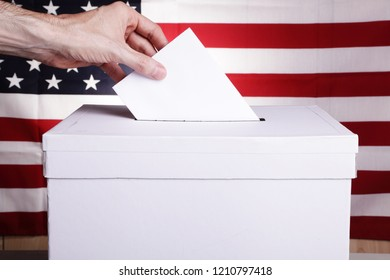 A man casting a vote. USA flag behind him