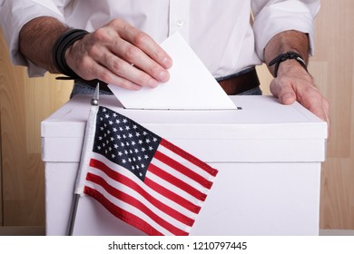 A man casting a vote. USA flag in front of the ballot box