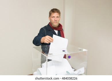 Man casts ballot in the ballot box. A man votes in the elections to the State Duma. Election candidates and parties. Visiting a polling station.