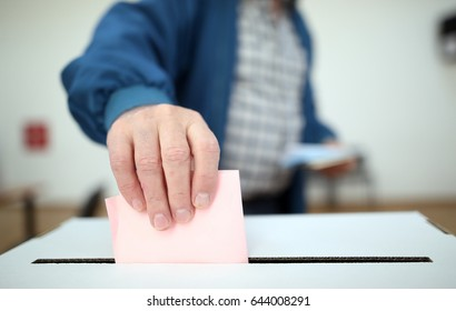 Man casts his ballot as he votes for the local elections at a polling station. Focus on hand.