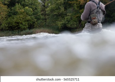 A man casts his fly rod into a river during the autumn