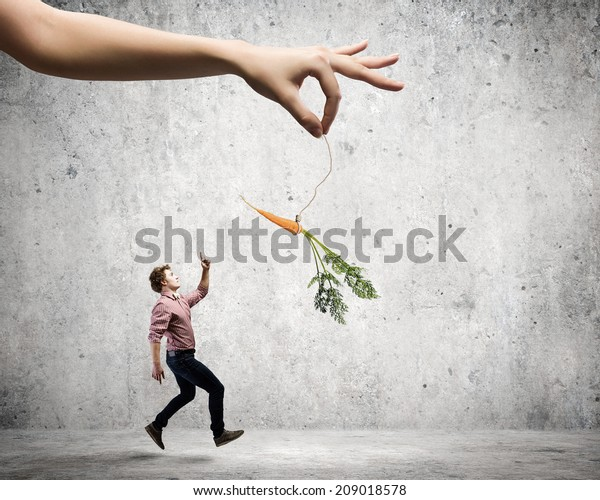 Man in casual chased with carrot hanging on rope
