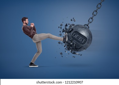 A man in casual clothes kicks a giant wrecking ball with a word DEBT written on it. Debt or insurance. Getting money back. Rebuilding your fortune.