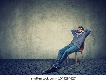 man in casual clothing sitting on chair and daydreaming