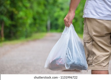 Man in casual cloths hold the plastic bags and walk on the street in the park