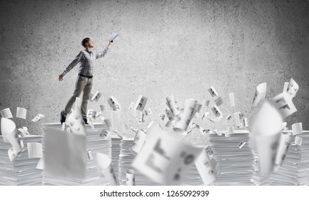 Man in casual wear keeping hand with book up while standing among flying documents with grey background. Mixed media.