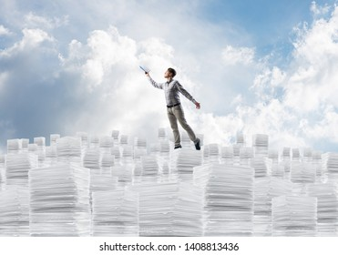 Man in casual wear keeping hand with book up while standing on pile of paper documents with cloudly skyscape on background. Mixed media.