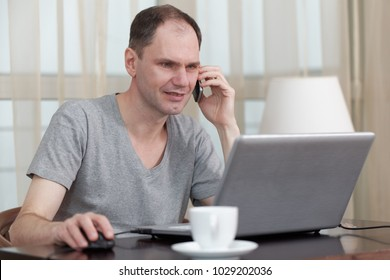 Man in casuals with laptop and mobile phone at home