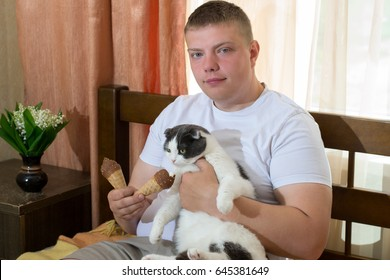 Man and cat eating ice cream cone in the bed
