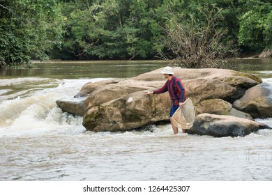 The man catching fish at the waterfall