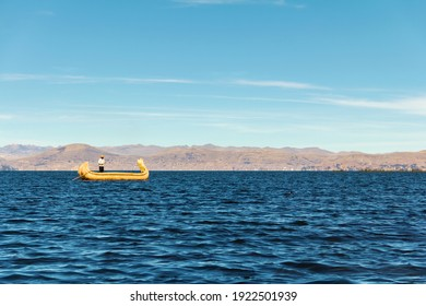 Man in cattail boat sailing on Titicaca lake, Puno