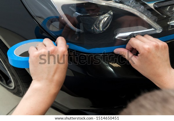 A man of Caucasian appearance with blue paper tape plasters a body element headlight with a black car to polish a paint and varnish and remove scratches in a vehicle wash and detailing workshop.