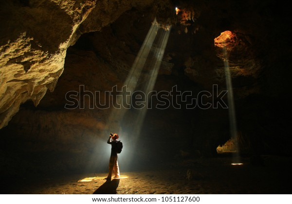 Man in cave exploration with ray of light