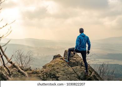 Man celebrating or praying in beautiful inspiring mountains sunrise. Hiker silhouette on mountain top hiking or climbing. Looking and enjoying inspirational sunshine landscape on rock.