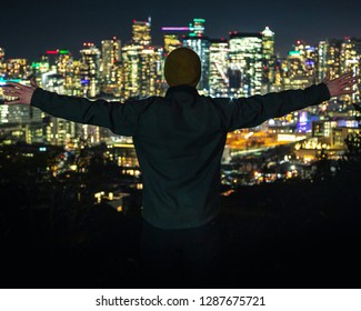 Man Celebrating Success with Hands Stretched Out on Bright City View at Night