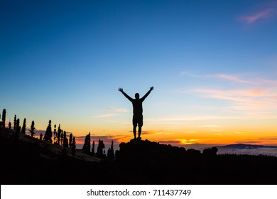 Man celebrating sunset with arms outstretched in mountains. Trail runner, hiker or climber with hands raised reached top of a mountain, inspirational landscape view on Tenerife, Canary Islands