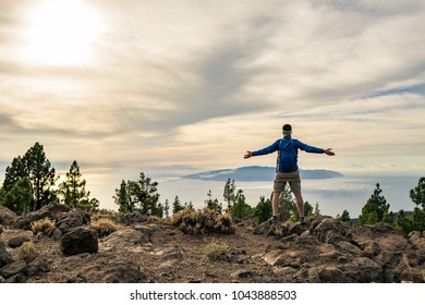 Man celebrating sunset looking at view in mountains. Trail runner, hiker or climber reached top of a mountain, enjoy inspirational landscape on rocky trail on Tenerife, Canary Islands