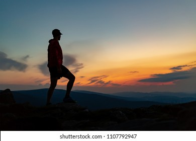 Man celebrating sunset on mountain top. Looking at inspiring view. Trail runner, hiker or climber reached mountain peak, enjoy inspirational landscape on rocky trail Karkonosze, Poland
