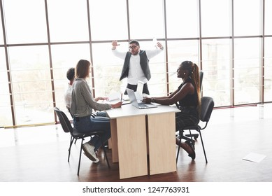 Man in the center gestures and talking. Group of freelancers working in the spacious office with big windows.