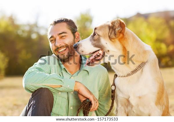 Człowiek i środkowoazjatycki pasterz chodzić w parku. Trzyma psa na smyczy.