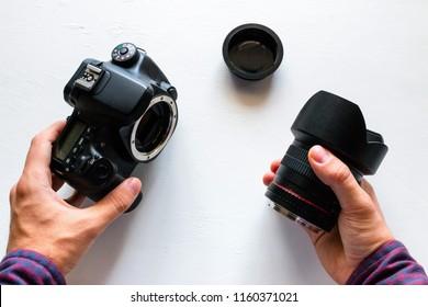 man changes lens on DSLR camera