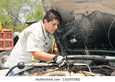 Man changes the oil to a truck. Monterrey , Mexico. May 16, 2010