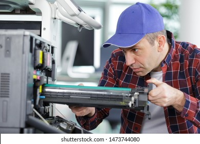 man changes the printer cartridge in the office