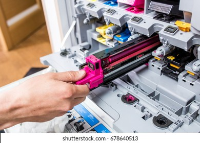 Man changes the printer cartridge in the office. Hand and color detail. Focus in the center.