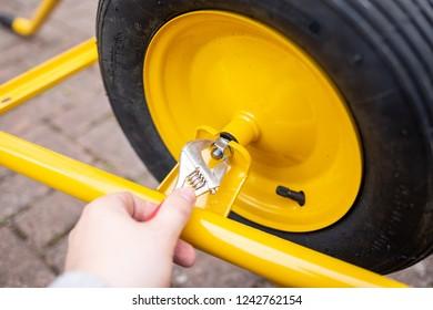Man changes the wheel of a wheelbarrow