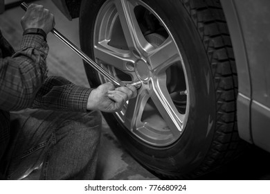 Man changing and fixing car wheel with long wrench in hand