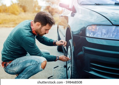 Man changing wheel on the car at the side of the road. Transportation, traveling concept
