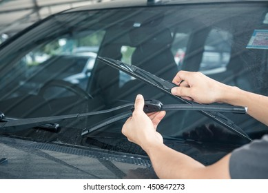Man is changing windscreen wipers on a car
