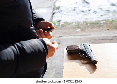 A man charges a gun with bullets in the street. Danger, murder, firearms, shooting range, sports entertainment.
